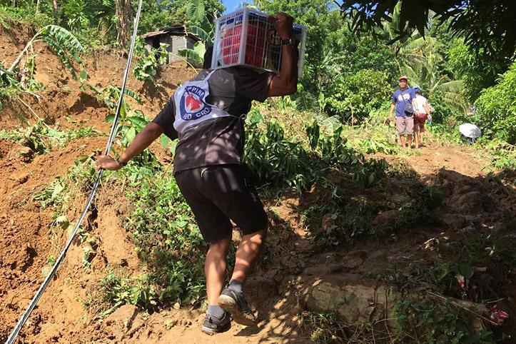 Foto: Helfer des Philippinischen Roten Kreuzes steigt mit Hilfsgütern einen Berg hoch