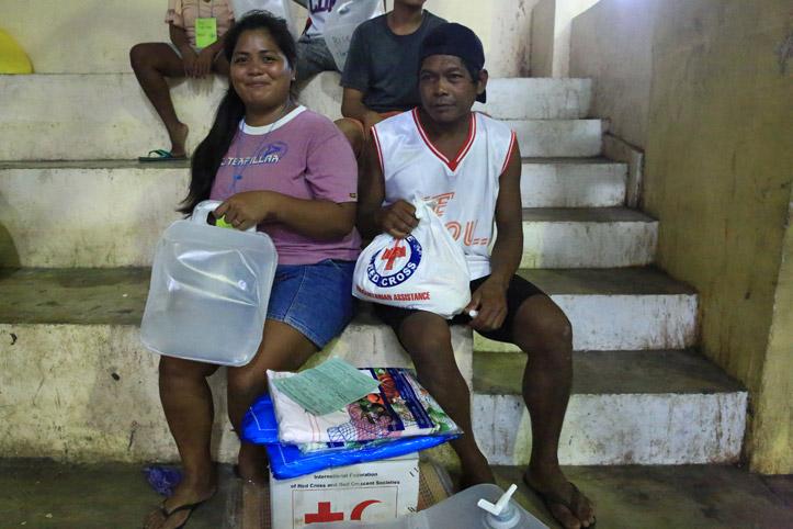 Foto: Hilfebedürftige Menschen mit Hilfegütern sitzen auf einer Treppe