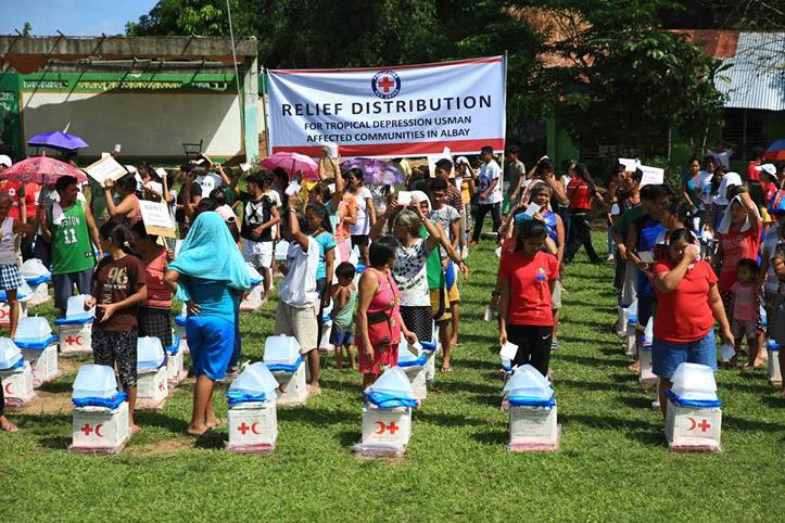 Foto: Menschen in den Philippinen mit Hilfsgütern auf einer Wiese