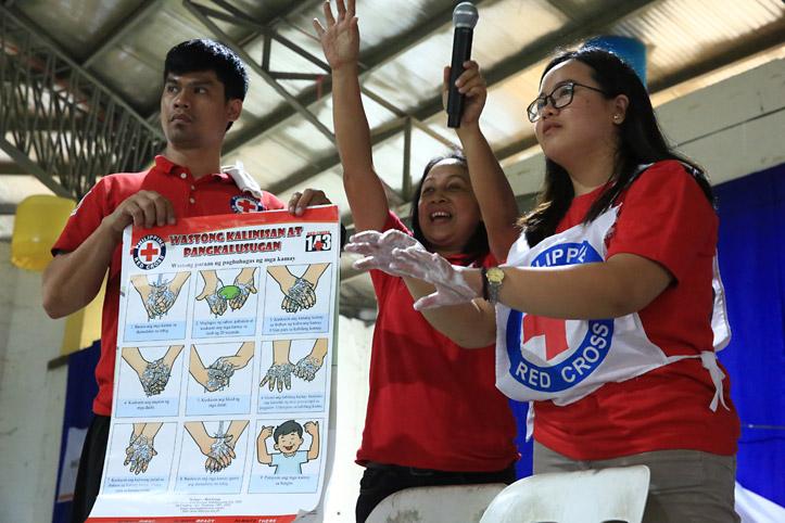 Foto: Rotkreuzhelfer zeigen ein Plakat über das Händewaschen