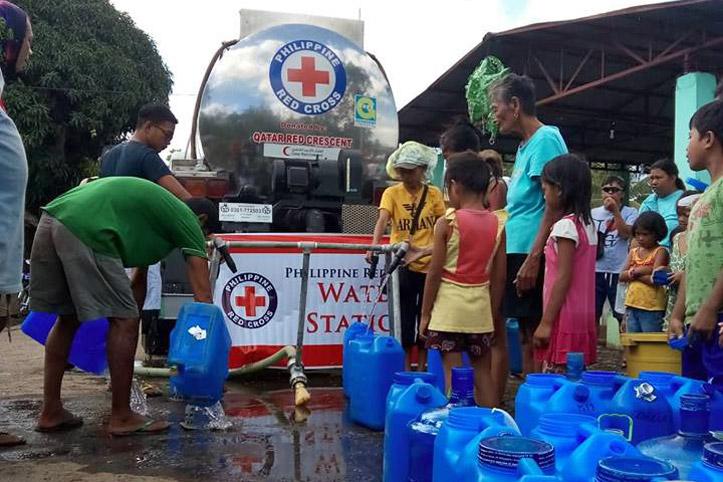 Foto: Kinder und ERwahcsene auf den Philippinen bei einer Hilfsgüterverteilung