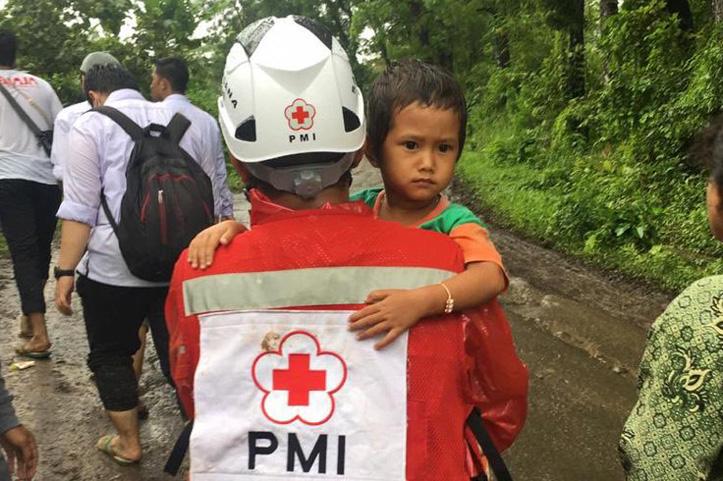 Rotkreuz-Helfer trägt Jungen nach Katastrophen in Indonesien