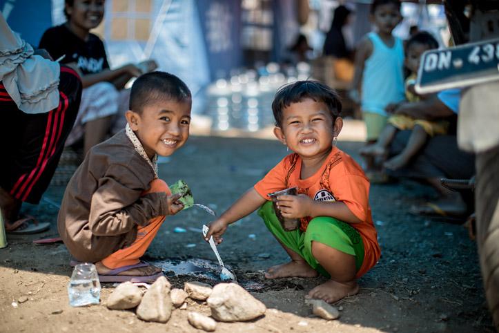 Zwei indonesische Jungen spielen auf dem Boden
