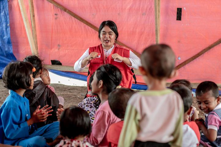 Indonesische Rotkreuz-Helferin spricht gestikulierend vor Kindergruppe
