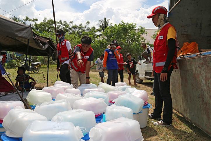 Rotkreuz-Helfer in Indonesien stellen Wasserbehälter bereit