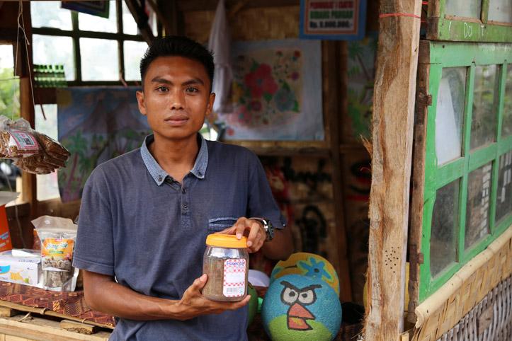 Junger Mann in Indonesien vor offenem Holzgebäude