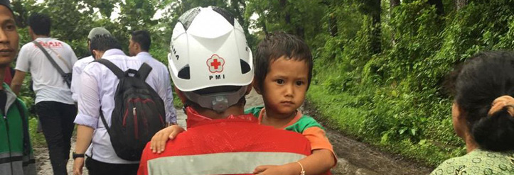 Rotkreuz-Helfer trägt einen indonesischen Jungen