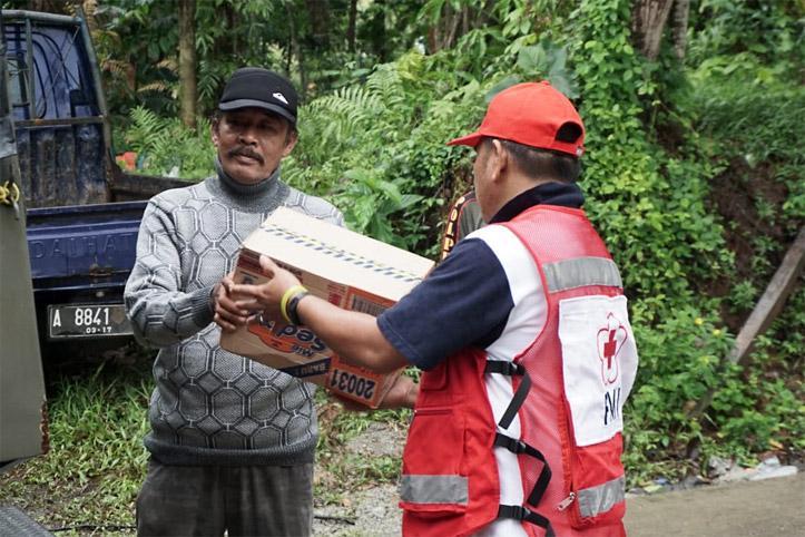 Zwei Männer in Indonesien übergeben sich Hilfsgüter
