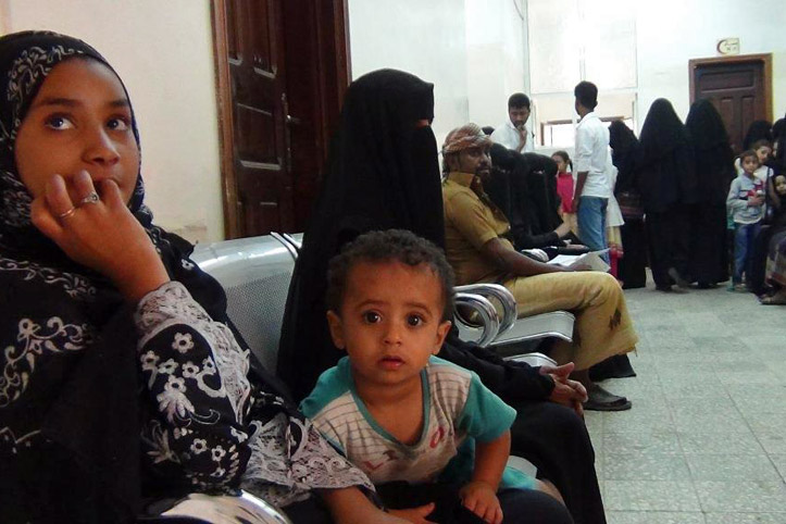 Foto: Jeminitische Mutter und ihr Kind mit anderen Menschen in einem Warteraum