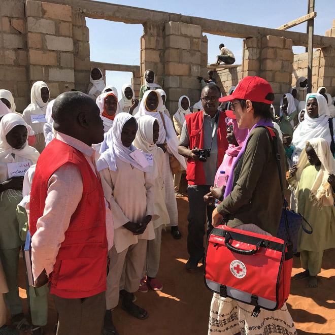 Foto: Gespräch einer DRK-Mitarbeiterin mit Schülerinnen und Lehrerinnen