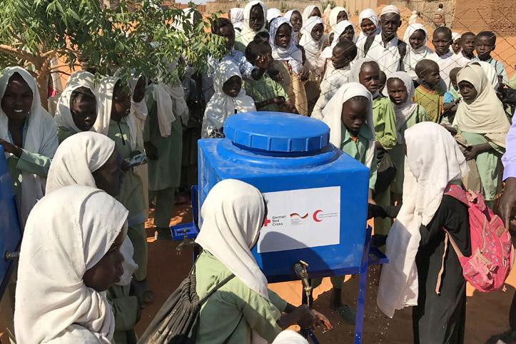 Foto: Sudanesische Mädchen sammeln sich um eine Handwascheinrichtung