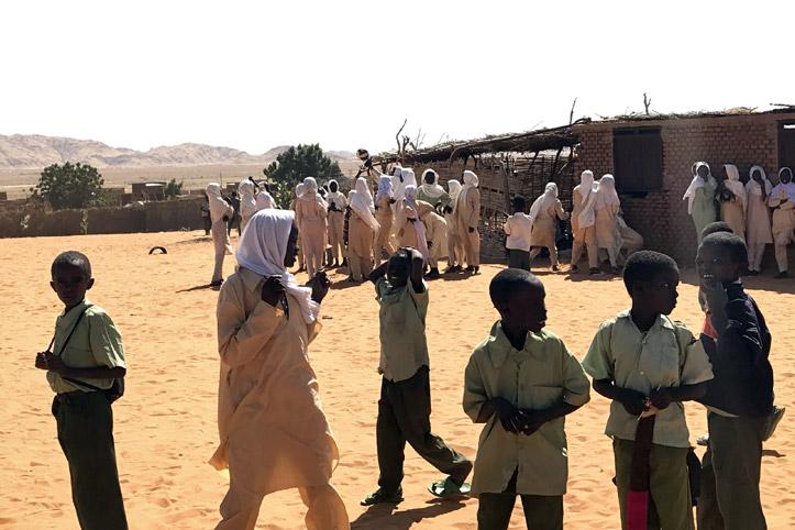 Foto: sudanesische Schulkinder in der Pause auf dem sandigen Schulhof