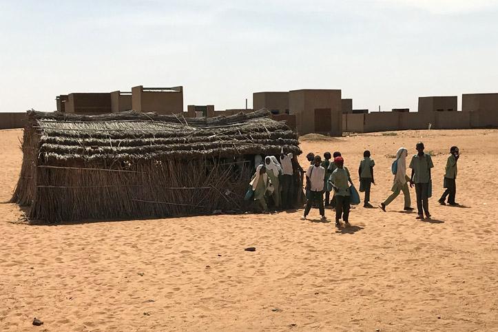 Foto: Kinder kommen aus einer Strohhütte