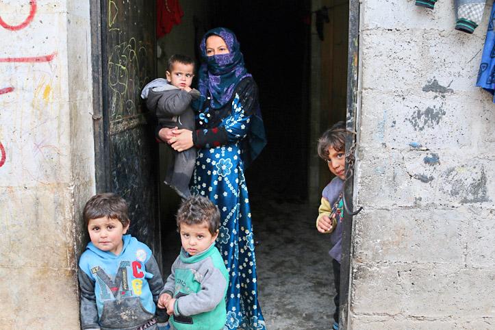 Foto: Eine junge syrische FRau mit vier Kinder in einem Hauseingang