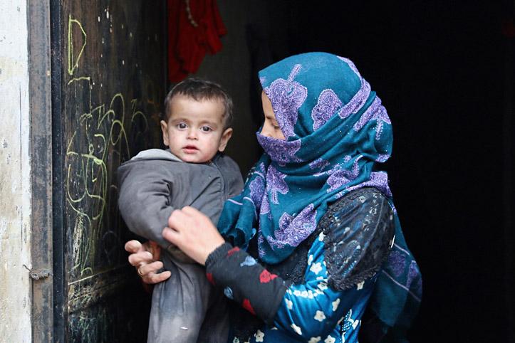 Foto: Junge syrische Mutter hält ihr Baby im Arm.