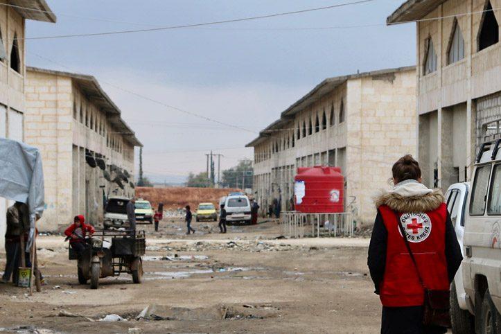 Foto: DRK-Mitarbeiterin läuft durch Vertriebenencamp in Syrien
