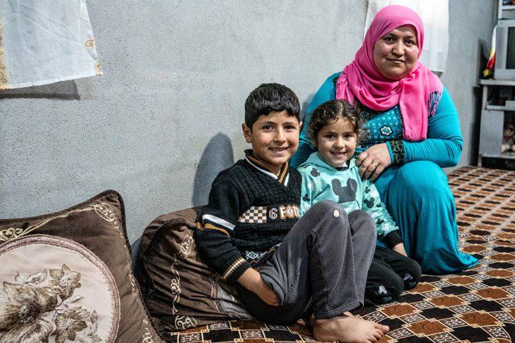 Foto: Eine syrische Mutter mit ihren zwei Kindern in ihrer Unterkunft im Irak