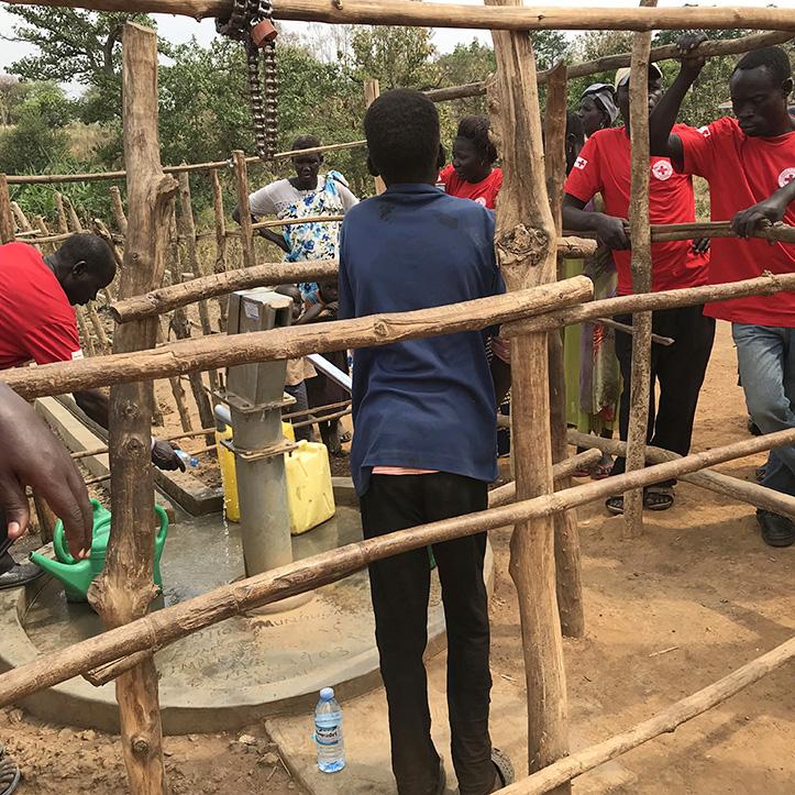 Foto: Menschen in Uganda an einem umzäunten Brunnen