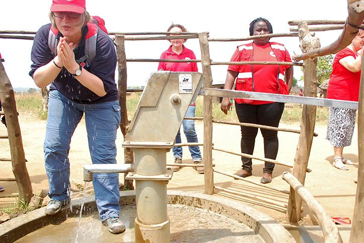 Foto: DRK-Mitarbeiterin erfrischt sich mit Wasser an einem neuen Brunnen in Uganda