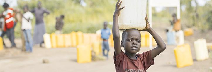 Foto: Junge in Uganda trägt einen Wasserkanister