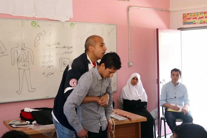 Foto: Lehrer erklärt Schülern einen Erste-Hilfe-Griff