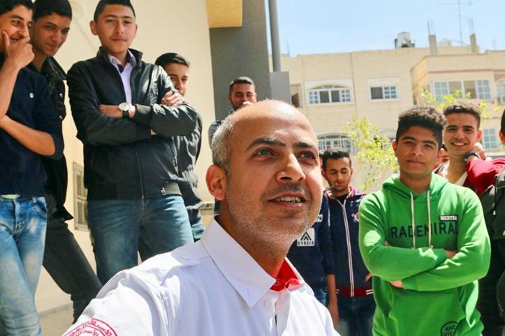 Foto: Rothalbmondhelfer und Schüler im Hintergrund