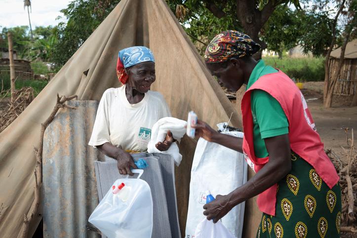 Foto: Helferin vom Roten Kreuz übergibt Hilfsgüter an eine Seniorin in Mosambik