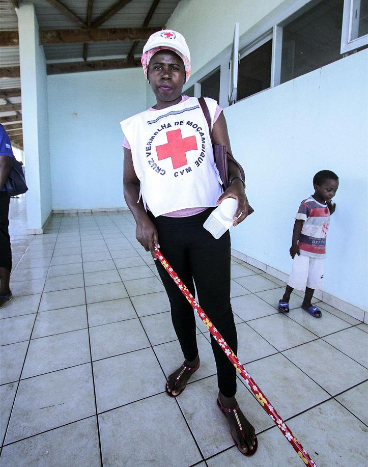 Foto: Eine Rotkreuzhelferin in Mosambik beim Boden-Wischen.