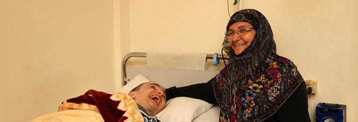 Lebanese mother at bed of disabled son