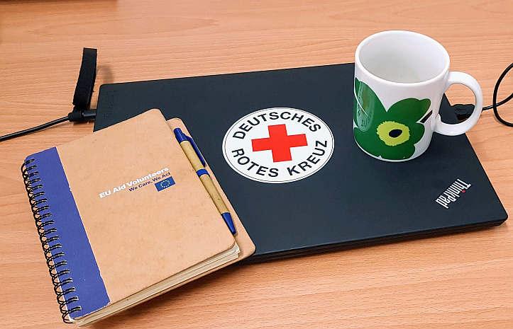 EU Aid Volunteer-Notizbuch, Laptop und Tasse