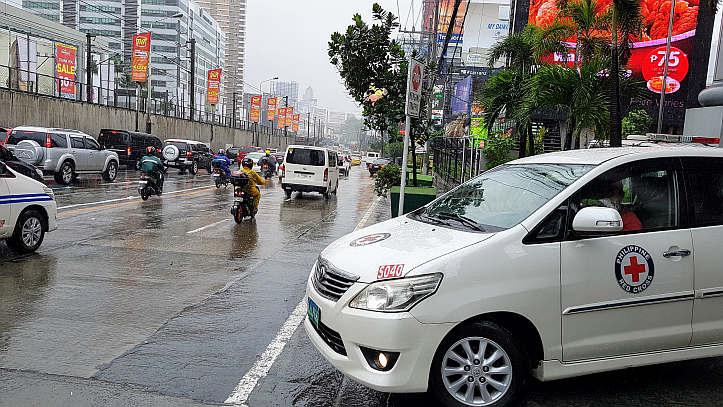 Straßenszene in Manila mit Rotkreuzwagen