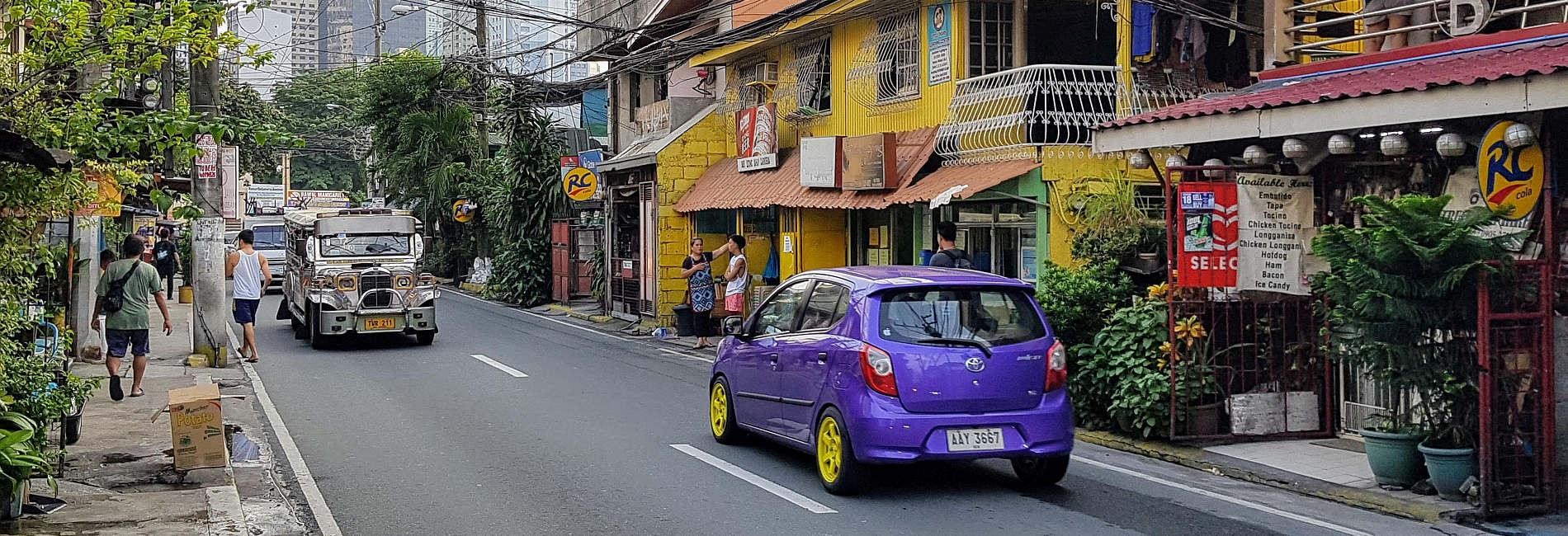 Straße in Manila mit Fahrzeugen und Passanten