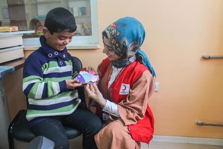 Foto: Gehörloser Junge und eine türkische Rothalbmondhelferin schauen sich eine Bastelei an