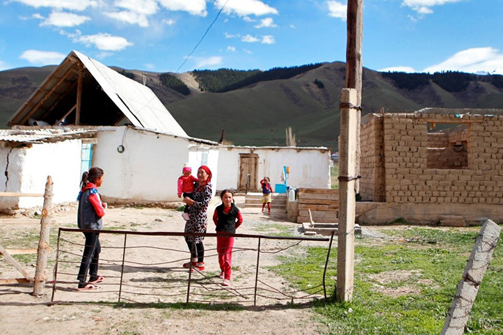 Familie in Kirgistan vor ihrem Gehöft mit Rohbau
