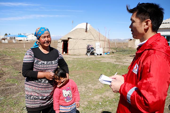 Helfer im Gespräch mit einer kirgisischen Mutter