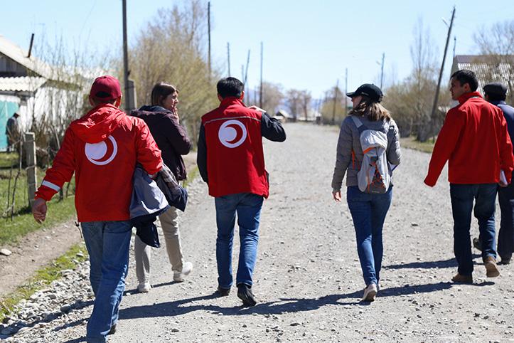 Rotkreuz- und Rothalbmondmitarbeiter laufen durch ein Dorf