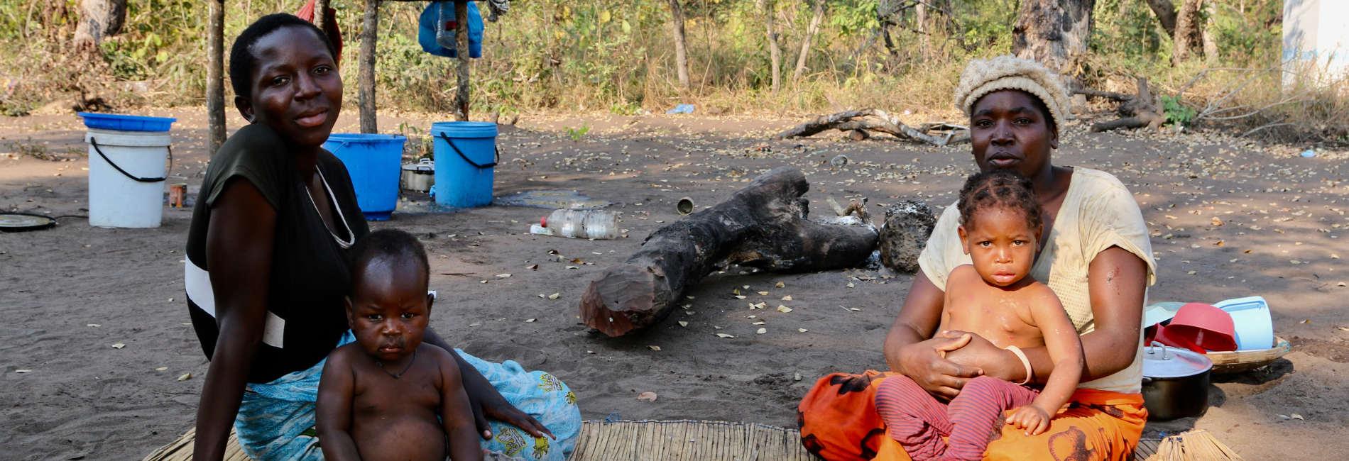 Zwei Mosambikanische Mütter mit Kindern auf dem Boden