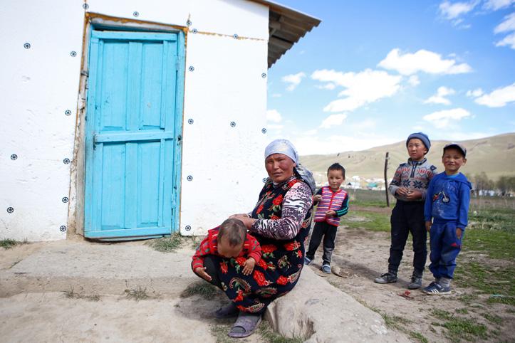 Foto: Kirgisische Mutter mit ihren Kindern vor einem Haus