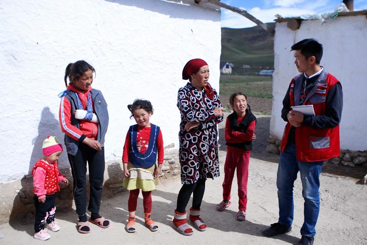 Rotkreuzmitarbeiter im Gespräch mit einer kirgisischen Familie