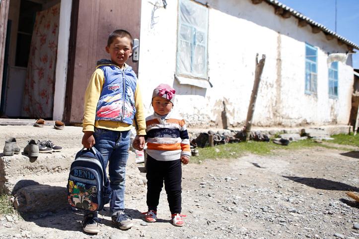 Zwei kirgisische Kinder vor einem einfachen Haus