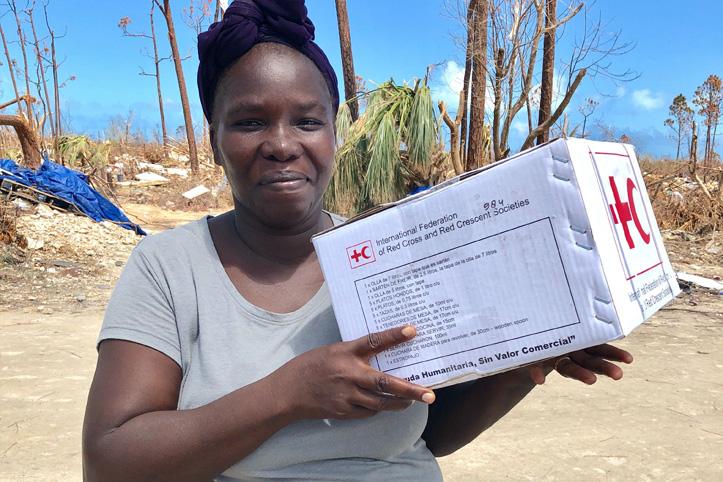 Foto: von Hurrikan Dorian betroffene Frau mit einem Hilfspaket