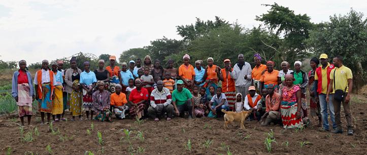 Gruppenbild: Mosambikaner und Mosambikanerinnen auf einem Feld