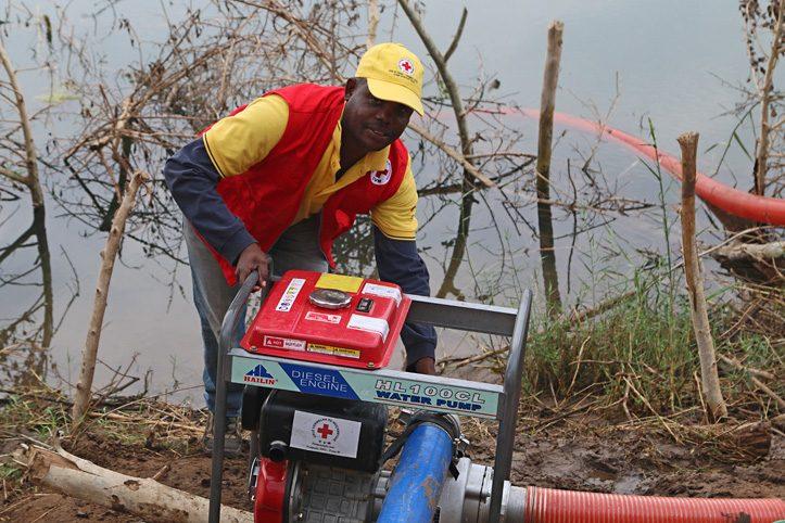 Mitarbeiter des Mosambikanischen Roten Kreuzes zeigt eine Wasserpumpe