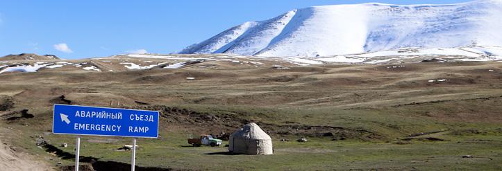 Landschaft in Kirgistan - Berg, Yurte und Straßenschild