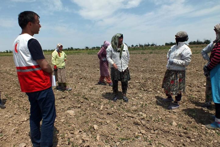 Foto: Rotkreuzmitarbeiter und Baumwollpflückerinnen auf einem Feld