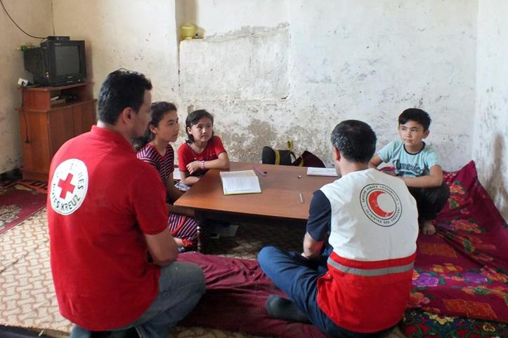 Foto: Rotkreuzmitarbeiter sprechen mit kirgisischen Kindern
