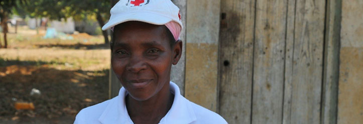 Rotkreuz-Freiwillige in Mosambik vor Bretterhütte