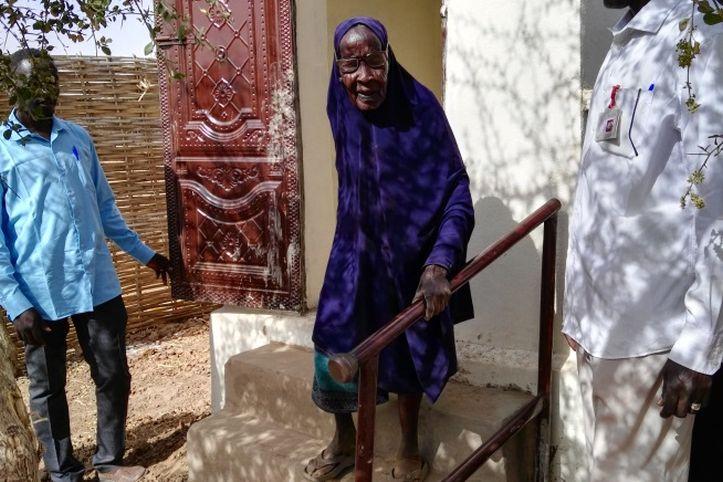 Alte Frau im Sudan auf einer Treppe einer Latrine