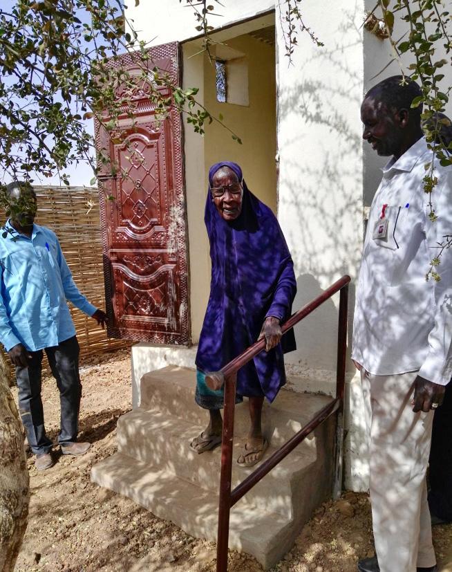 Foto: Sudanesische seniorin auf den Treppen einer neuen Latrine