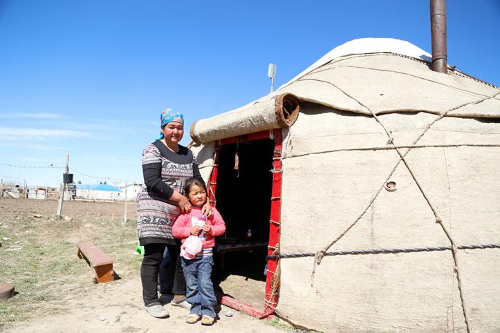 Kirgisin mit ihrer Tochter vor einer Jurte